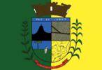 """A Bandeira de Ibiporã tem as cores verde e amarela e no seu centro, o Brasão do Município.Na parte superior do brasão há uma frase latina """"Pax et Labor"""", que significa """"Paz e Trabalho"""". Na parte central, o escudo tem os seguintes símbolos:   - Um motivo natural: representado pelo Morro do Guarani;  - Um motivo econômico: representado por fazendas de café, cortadas por estradas;  - Um motivo de situação: representado por um pinheiro araucária (que representa o Estado do Paraná) e um homem lavrando a terra;  - Um motivo primordial: que mostra os ribeirões que cortam o Município.  Contornando o brasão, existe à esquerda um ramo de café frutificado e à direita um ramo de milho como representantes da economia municipal. O brasão é coroado por um mural dourado. Em sua parte inferior, possui uma faixa em vermelho com o nome de Ibiporã e a data da instalação oficial do Município: 08/11/1947."""